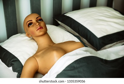Naked plastic woman humanoid laying alone on king size double bad.