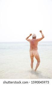 Naked senior man running into the sea