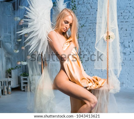 Naked Sexy Girl In White Wings On A Swing In The Studio Posing Hiding A Gold