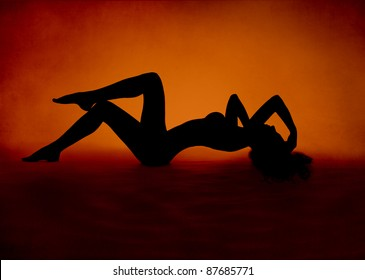 Naked sexy woman silhouette lying at red orange background