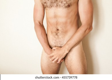 Naked sporty Caucasian man cover his genitals with hands, male body beauty, close up studio photo