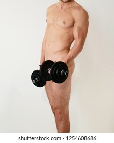 Naked sporty man cover his genitals with dumbbell, male body beauty, close up studio photo on white background