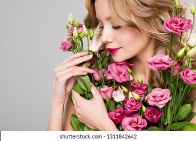 naked tender spring young woman holding bouquet of Eustoma flowers isolated on grey