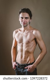 Naked torso of a young, slim, pumped-up man on a beige background. Tight naked attractive man in black jeans. Beautiful muscle relief