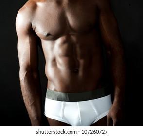 Naked underwear male model closeup shot over black background