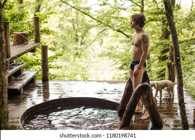 naked to the waist guy is enjoying the beauty of landscape while standing in front of the whirlpool. holiday and vacation concept. side view full length photo