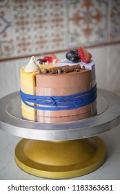 Naked wedding birthday cake. Rustic layer homemade cake with cream. Dessert decorated with chocolate and fruits. Selective focus. Piece of cake. Vegan raw cake.