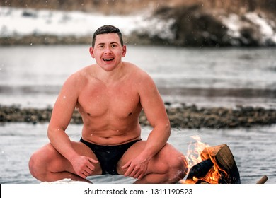naked wet man (walrus) in the winter on the river after swimming warm up by the fire