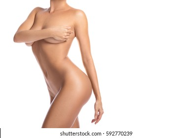 Naked woman covering her beautiful body with hands on white background