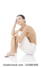 Naked woman covering her self with towel on white background.