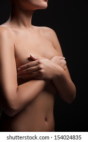 Naked woman. Cropped image of naked woman covering breast with hands while standing against black background