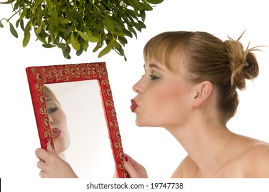 Naked woman kissing herself in a mirror under mistletoe isolated on white