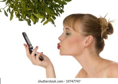 Naked woman kissing a mobile phone under mistletoe on white background