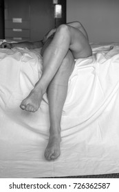 naked woman with legs dangling in the bed