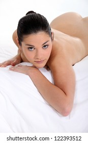 Naked woman lying on her bed