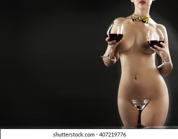 naked woman on a dark background with wine glasses and a martini glass