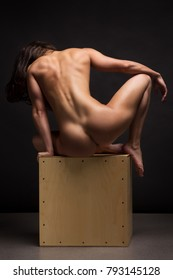 Naked woman on wooden box.