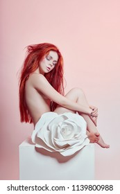 Naked woman with red hair sitting near a large paper flower. Beautiful long hair girl, beautiful body. Artificial paper rose flower on a woman's body. Hair and body care, perfect skin