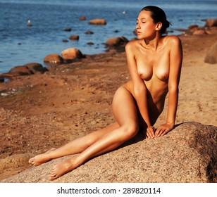 naked woman sitting on stone, beach, sunset