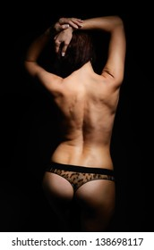 Naked woman is standing back. She has lifted the arms on her head. Her sexy body is photographed in the dark with a few highlights.
