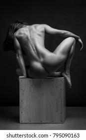 Naked woman Yoga on black background. Fine art photo of female body.
