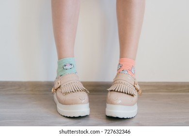 Naked women`s feet in feminine business bright leather shoes with tankette and white sole standing at home. Female feet in mismatched cotton colorful socks. Innocence and youth lifestyle. Odd girl