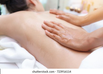 Naked young Asian female draped with a towel, skin glistening with oil, being rubbed down by a professional massager , Thai Aromatherapy Oil Massage in Spa salon