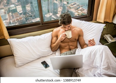Naked young man with muscular body on bed with mug or cup in hand with coffee or tea, looking at laptop computer screen