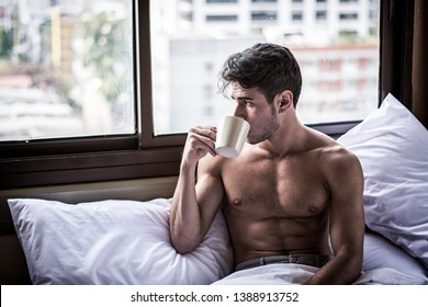 Naked young man with muscular body on bed with mug or cup in hand with coffee or tea