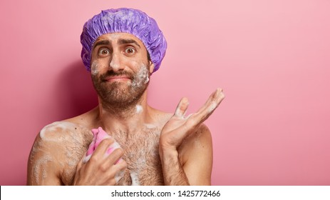 Naked young man with wet body and foam, rubs himself with sponge, takes shower, wears bath cap, has confused facial expression, raises hand in bewilderment, isolated over pink wall, empty space