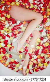 Naked young woman in bath with rose petals