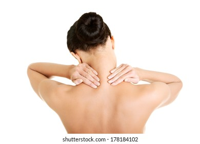 Naked young woman holding hands on neck in back pain. Brunette standing exposing back, shoulder, neck and hands. Isolated on the white background.