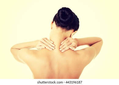 Naked young woman holding hands on neck in back pain.
