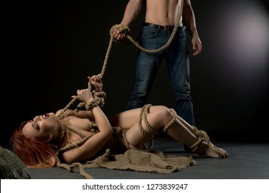 Naked young woman tied with rope near man in jeans