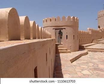 Nakhal Fort, Oman - April 07, 2004: female european tourist stands in a watchtower and takes a photo - a part of the wall can also be seen