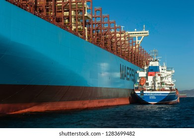 Nakhodka, Russia - January 12, 2019: Tanker Ostrov Sakhalin bunker container ship Maastricht Maersk standing in the roadstead.