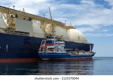 Nakhodka, Russia - June 21, 2018: Tanker Zaliv Vostok is engaged in bunkering LNG-tanker Cygnus Passage is anchored in the road.