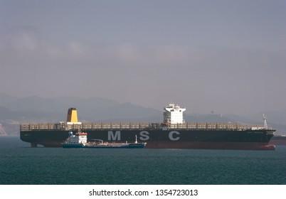 Nakhodka. Russia - March 17, 2019: Bunkering tanker Zaliv Nakhodka a large container ship MSC Trieste.
