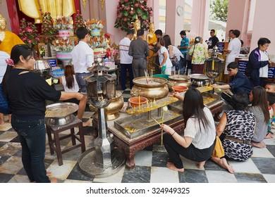 NAKHOM PATHOM, THAILAND - APRIL 09, 2012: Unidentified people burn candles in Nakhom Pathom chedi, Thailand.