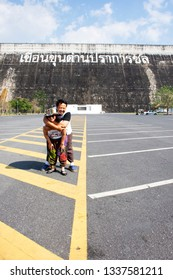 NAKHON NAYOK, THAILAND - JANUARY 18 : Asian thai women mother and son travel posing and playing on the parking front of Khun Dan Prakan Chon Dam on January 18, 2017 in Nakhon Nayok, Thailand