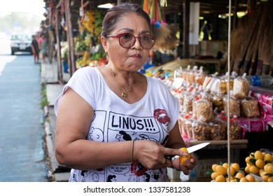 NAKHON NAYOK, THAILAND - JANUARY 18 : Asian thai old women test eat and buy shopping Marian plum or gandaria or plum mango on stall for sell at local shop on January 18, 2017 in Nakhon Nayok, Thailand