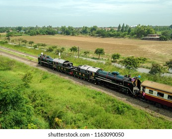 NAKHON PATHOM, THAILAND - AUG 12, 2015 : Old Thai Steam locomotive drives on the railway pass through the rice field in Nakhon Pathom province  the suburb of Thailand.