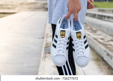 NAKHON PATHOM, THAILAND - SEPTEMBER 30, 2017 : Woman holding adidas superstar  white/black shoes with popular fashion thailand.