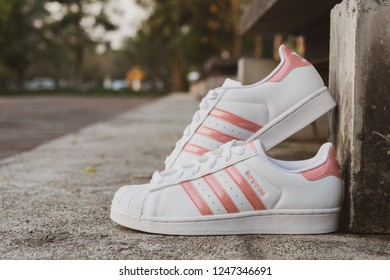 NAKHON PATHOM, THAILAND-NOVEMBER 17, 2018:Adidas superstar J white/pink shoes with popular fashion for women on cement floor outdoor in Thailand.