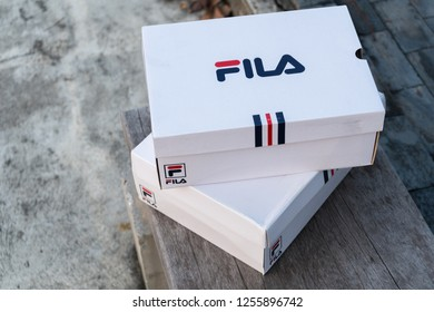 NAKHON PATHOM, THAILAND-NOVEMBER 17, 2018:Box Fila shoe, model disruptor 2 and disruptor 2 point, Fila is one of the world's largest sportswear manufacturing companies., shot outdoor on wood floor