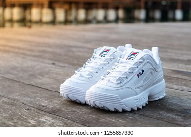 NAKHON PATHOM, THAILAND-NOVEMBER 17, 2018:Fila shoe, model disruptor 2 white popular, shot outdoor on wooden floor in Thailand., Fila is one of the world's largest sportswear manufacturing companies.