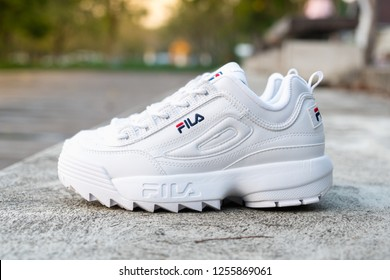 NAKHON PATHOM, THAILAND-NOVEMBER 17, 2018:Fila shoe, model disruptor 2 white popular, shot outdoor on cement floor in Thailand., Fila is one of the world's largest sportswear manufacturing companies.