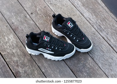 NAKHON PATHOM, THAILAND-NOVEMBER 17, 2018:Fila shoe,model disruptor 2 point black, shot outdoor on wooden floor in Thailand., Fila is one of the world's largest sportswear manufacturing companies.