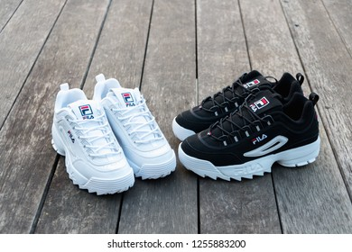 NAKHON PATHOM, THAILAND-NOVEMBER 17, 2018:Fila shoe,model disruptor 2 point black and disruptor 2 white, shot outdoor on wooden floor in Thailand.,