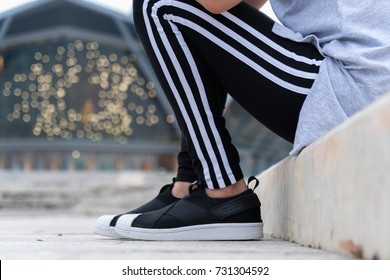 NAKHON PATHOM, THAILAND-SEPTEMBER 30, 2017 :A woman wear adidas sports sweatpantst and shoes on. A German multinational corporation that designs and manufactures sports shoes, clothing and accessories